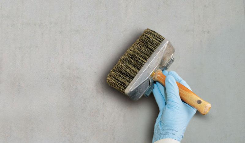 Maler mit Deckenpinsel beim streichen