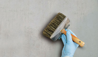 Flächenstreicher auf grauer Wand